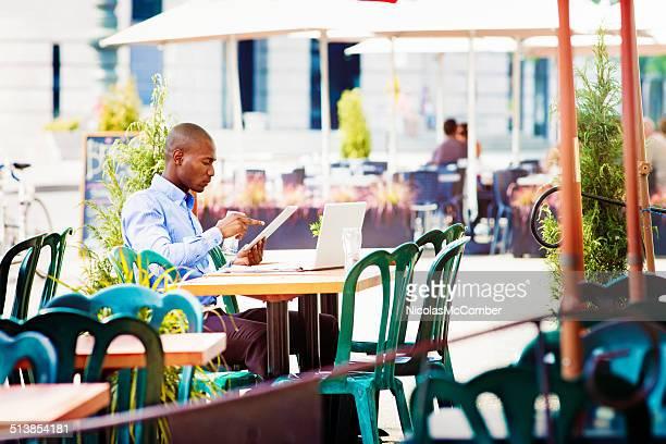 Employé de bureau travaillant dans un café en plein air