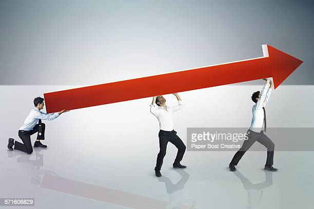 Office workers all carrying one giant red arrow