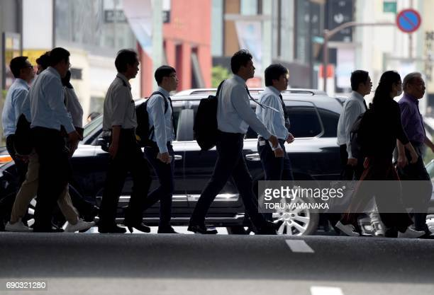 Office workers and pedestrians cross a street in Tokyo on May 31 2017 Japanese employers are scrambling to find staff unemployment is at its lowest...
