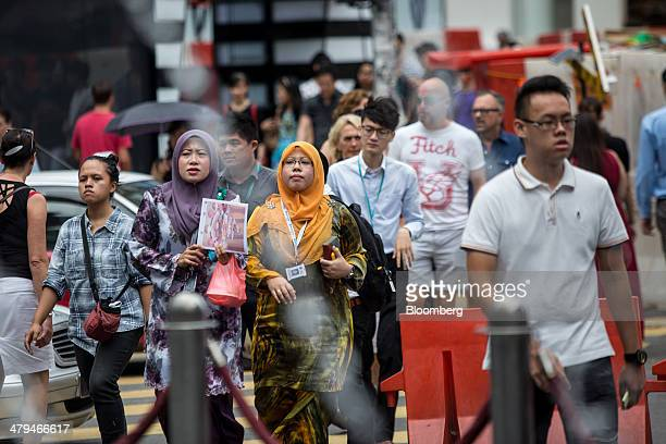 Office workers and tourists cross a road during lunch hour in Kuala Lumpur, Malaysia, on Tuesday, March 18, 2014. Malaysia, aspiring to become a...