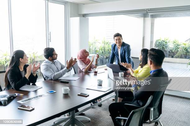 office workers applauding manager in business meeting - respect stock pictures, royalty-free photos & images