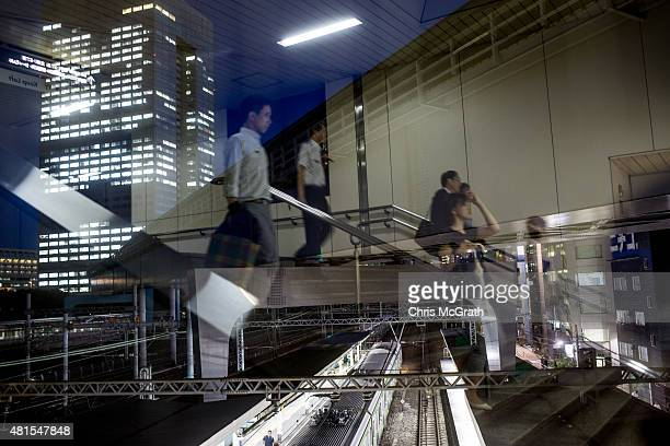 Office workers are seen reflected in a window as they walk to a train station in front of the Toshiba Corporations Tokyo headquarters on July 22 2015...