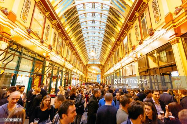 Office workers drinking beer at Leadenhall Market on a Friday evening, London, England