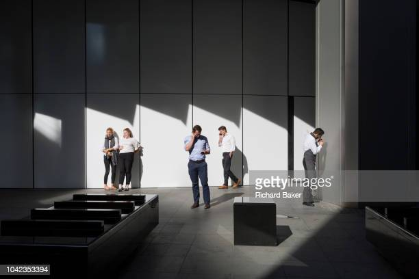Office workers enjoy the warmth of autumnal sunshine outside the Willis Towers Watson building on Fenchurch Avenue in the heart of the capital's...