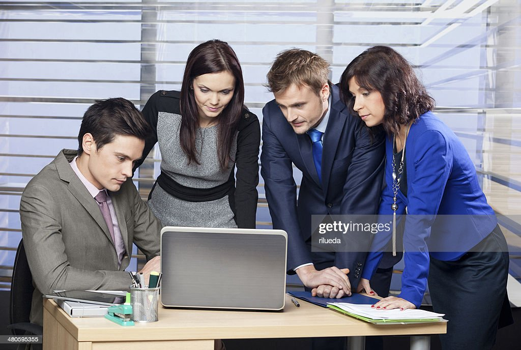 Office workers gathered around laptop : Stock Photo