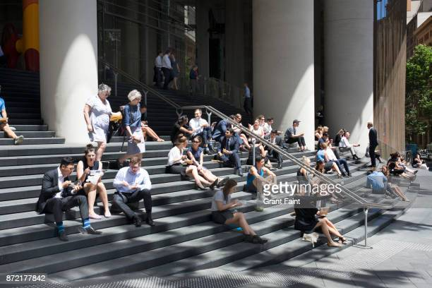 Office workers having lunch on steps of tower