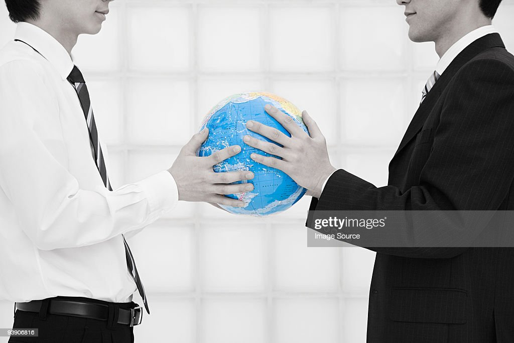Office workers holding globe : Stock Photo