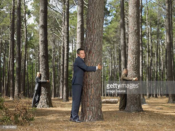 Office workers hugging trees