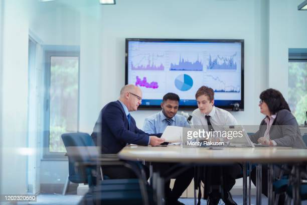 office workers in meeting with graphs and charts - shirt stock pictures, royalty-free photos & images
