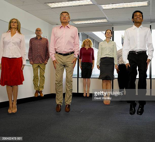 Office workers jumping in empty office, arms by side
