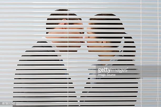 office workers kissing - cornuto foto e immagini stock