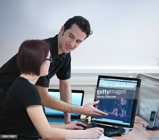 Office workers looking at CAD drawings in carbon fibre factory