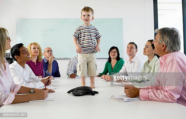 Office workers looking up at boy (18-21 months) standing on table