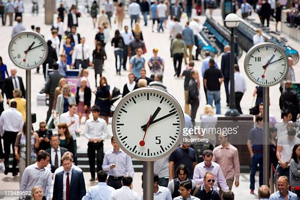 Office workers pass clocks in the Canary Wharf business and shopping district in London UK on Friday July 12 2013 Recent data suggest Britain's...