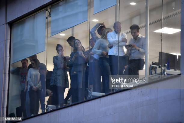 Office workers peer out of the windows of Leadenhall Market near London Bridge in central London on November 29 2019 after reports of shots being...