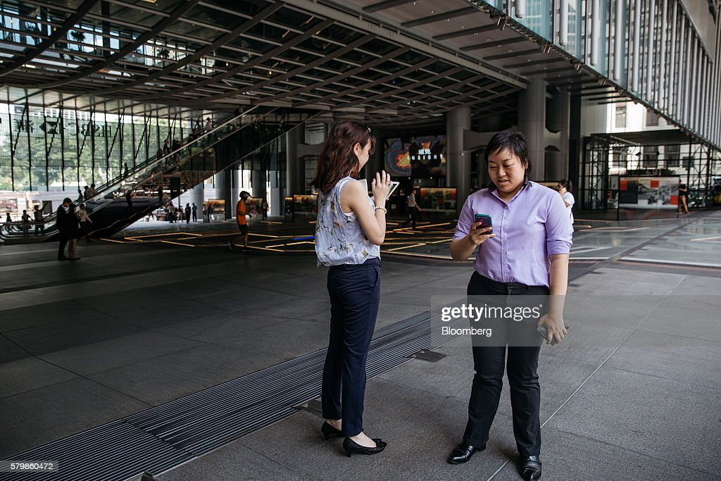 Office workers play Nintendo Co.'s Pokemon Go augmented-reality game, developed by Niantic Inc., on their smartphones at the HSBC Holdings Plc headquarters building during lunch hour in Hong Kong, China, on Monday, July 25, 2016. After debuting in the U.S. earlier this month, Pokemon Go launched in Japan on Friday and became available in Hong Kong on Monday. Photographer: Anthony Kwan/Bloomberg via Getty Images