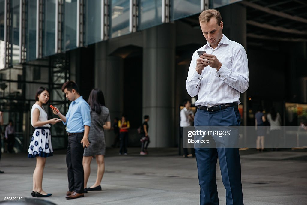 Office workers play Nintendo Co.'s Pokemon Go augmented-reality game, developed by Niantic Inc., on their smartphones outside the HSBC Holdings Plc headquarters building during lunch hour in Hong Kong, China, on Monday, July 25, 2016. After debuting in the U.S. earlier this month, Pokemon Go launched in Japan on Friday and became available in Hong Kong on Monday. Photographer: Anthony Kwan/Bloomberg via Getty Images