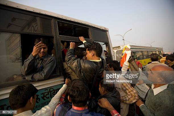 Office workers run for a bus during morning rush hour February 18 2008 in New Delhi India The city has the largest natural gas bus fleet in the world...
