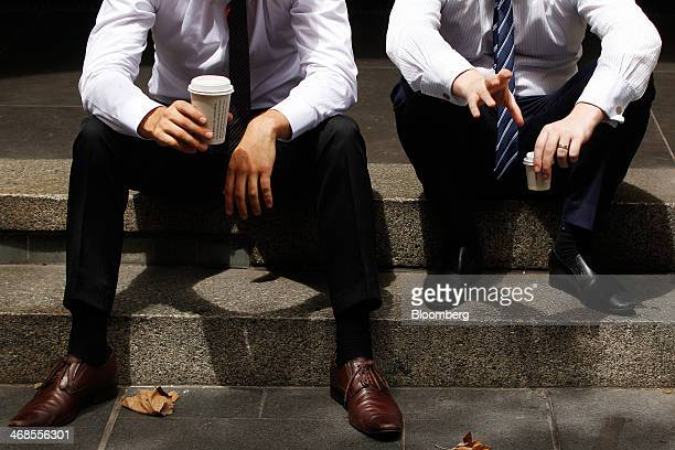 Office workers sit with cups of coffee at Martin Place in the central business district of Sydney Australia on Monday Feb 10 2014 Australian business...