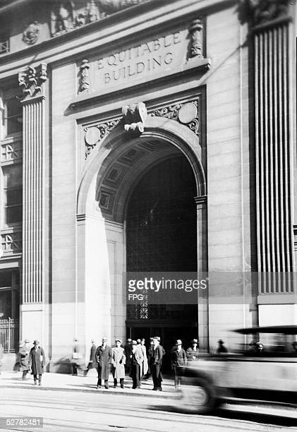 Office workers stand on the sidewalk in front of the arch entrance to the Equitable Building at 120 Broadway in downtown Manhattan, New York, New...