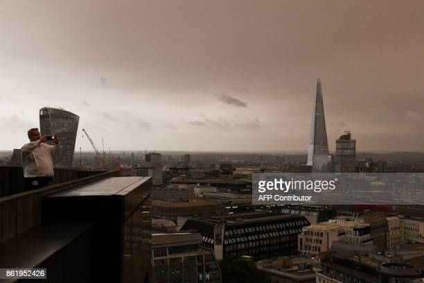 TOPSHOT Office workers stand on their balcony to photograph the darkened sky over London on October 16 2017 caused by warm air and dust swept up by...