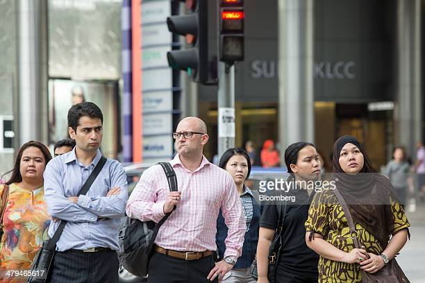Office workers wait to cross a road at the end of the work day in Kuala Lumpur, Malaysia, on Tuesday, March 18, 2014. Malaysia, aspiring to become a...