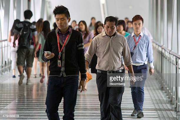 Office workers walk along a walkway during lunch hour in Kuala Lumpur, Malaysia, on Tuesday, March 18, 2014. Malaysia, aspiring to become a developed...