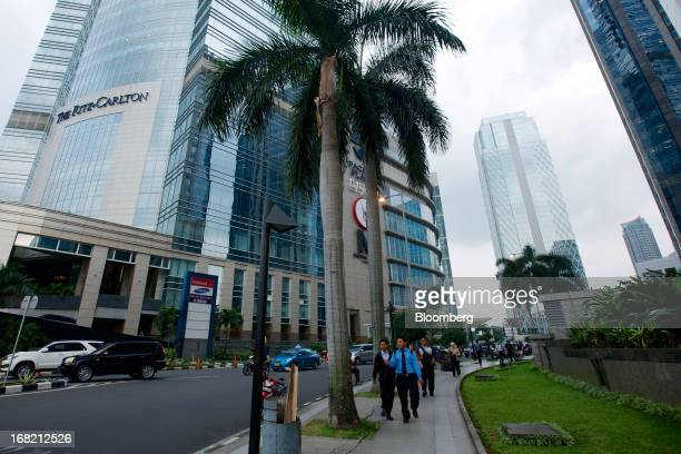 Office workers walk past the RitzCarlton Hotel left and the Pacific Place shopping mall center in the central business district of Jakarta Indonesia...