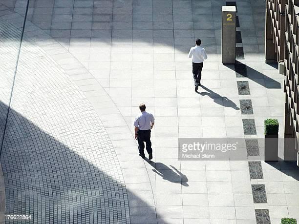 office workers walking across plaza - pedone ruolo dell'uomo foto e immagini stock