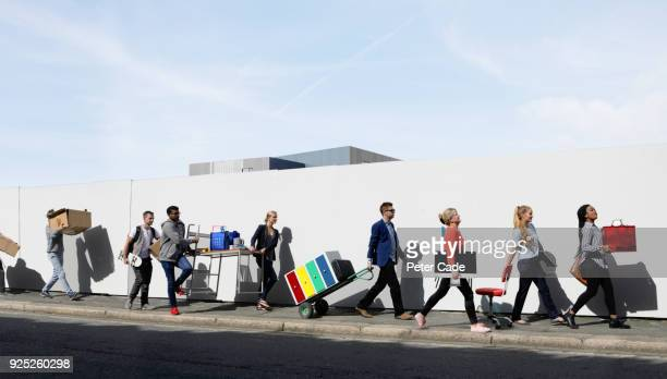 office workers walking in a line down street carrying office equipment - parade stock pictures, royalty-free photos & images