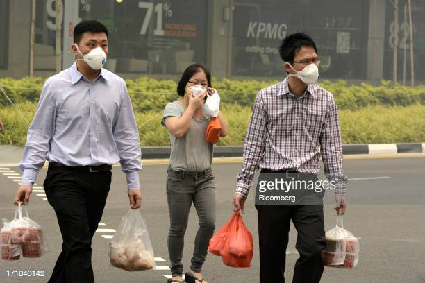 Office workers wearing face masks carry bags of takeaway food as they cross a road during lunch hour in Singapore, on Friday, June 21, 2013....