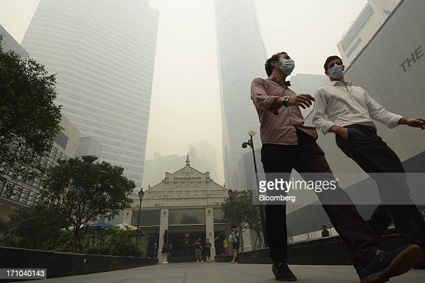 Office workers wearing face masks walk through Raffles Place as office buildings stand shrouded in smog in Singapore, on Friday, June 21, 2013....