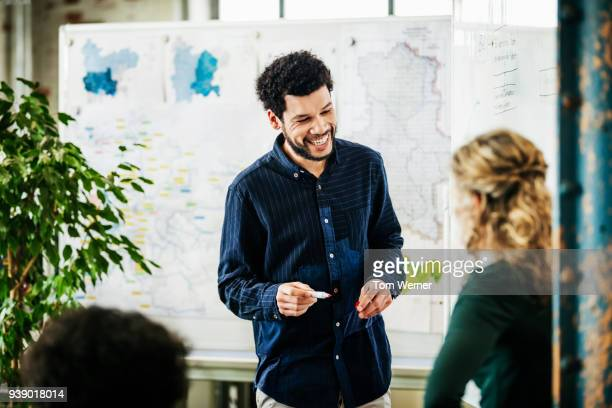 Office Working Smiling While Talking To Colleague