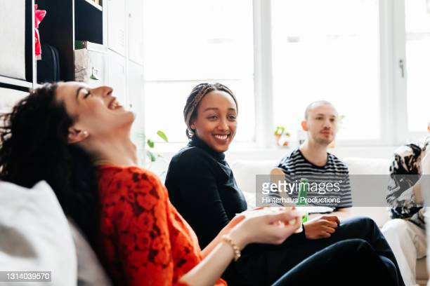 office workmates socializing with drinks in office - relaxation stock pictures, royalty-free photos & images
