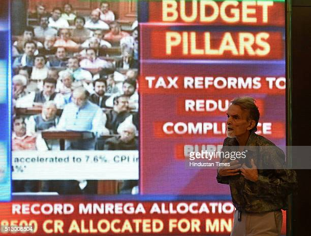 Officegoers walk past a digital screen showing Indian Finance Minister Arun Jaitley delivering his Budget speech at Parliament in New Delhi at the...