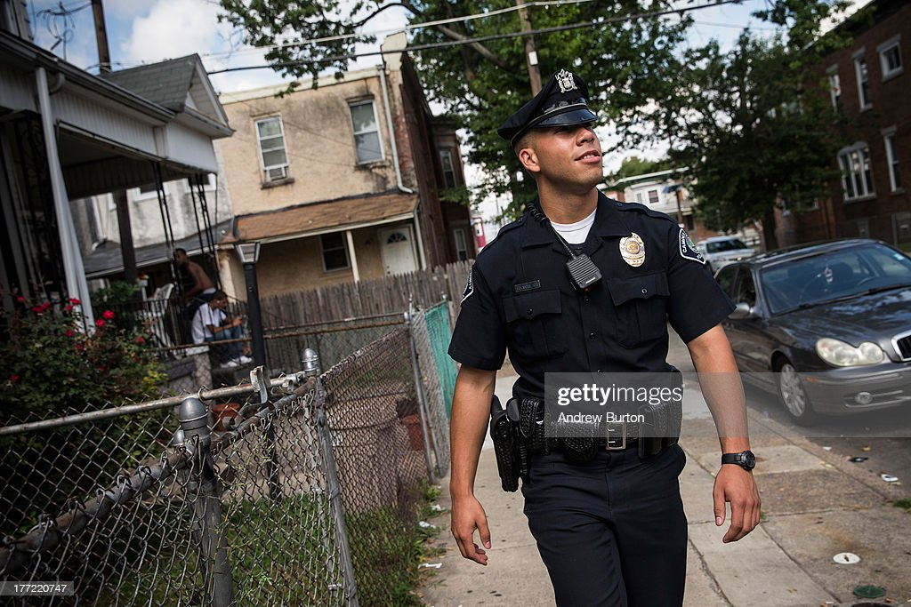 Officer Adam Fulmore, of the Camden County Police Department, goes on a foot patrol on August 22, 2013 in the Parkside neighborhood of Camden, New Jersey. The town of Camden, which was once a large industrial town but watched it's population dwindle as manufacturing left, has been marred with societal problems including high unemployment, crime, murder and heavy drug trafficking for decades. The Camden County Police Department was officially created in May, 2013, after the unionized Camden Police department was disbanded. The overhaul, which was supported by New Jersey Governor Chris Christie, has been considered unprecendented and has been closely watched around the country. The new force currently has approximately 280 members, and will reach full size by December, with 400 members. Early signs suggest the overhaul has been effective - The Wall Street Journal reported earlier this month that Camden murder rates fell 29% from May, 2013 to July 2013, compared to the same period last year. Absentee rates of the CCPD is also lower: approximately 5% of officers have been reported absent so far, compared to approxmiately 30% of the Camden Police Department prior to the change in command.
