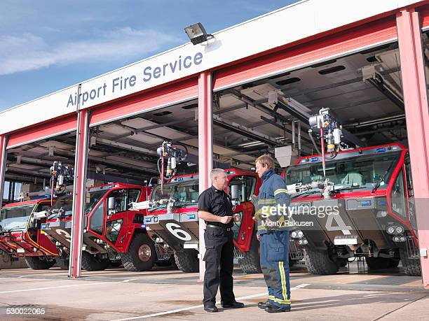 Officer and fireman in front of fire engines in airport fire station