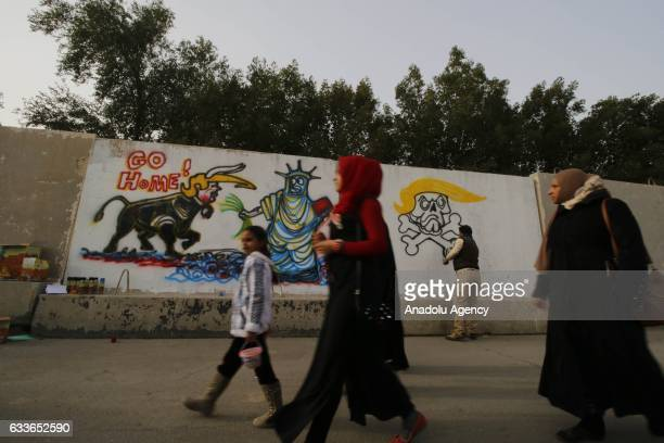 Officer Arqan Bahadili paints a mural on a barrier criticizing US President Donald J Trump's executive order banning entry of 7 Muslimmajority...
