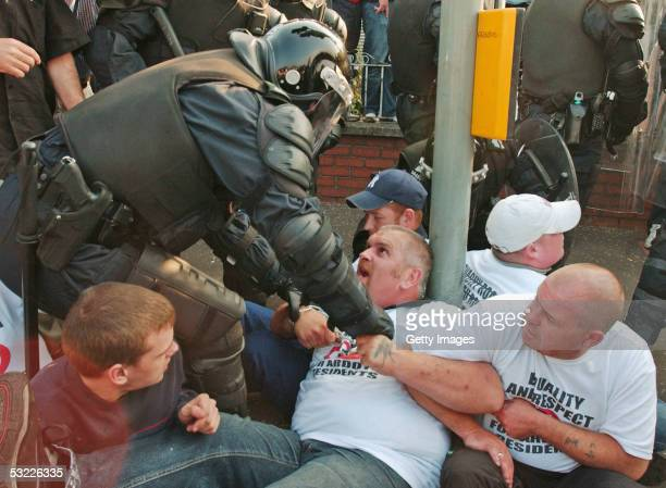 officer attempts to remove a sit down protester on the Crumlin Road on July 12 2005 in Belfast Northern Ireland Catholic residents of the Ardoyne...