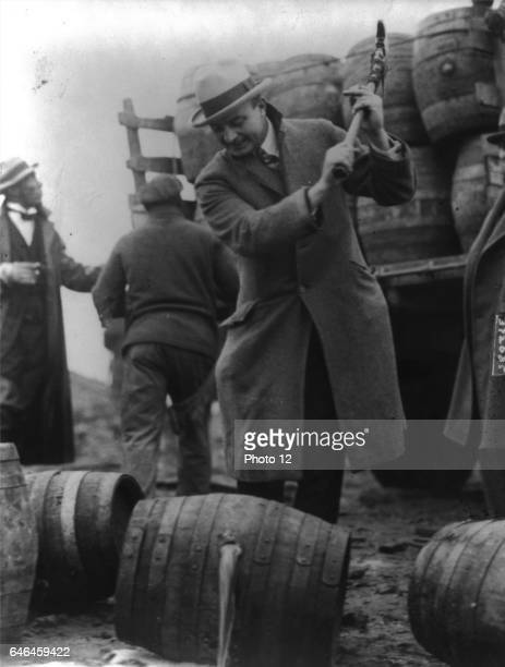 FBI Officer breaks a confiscated barrel of beer as part of the prohibition campaign against alcohol in the USA in the 1920's Date 1924