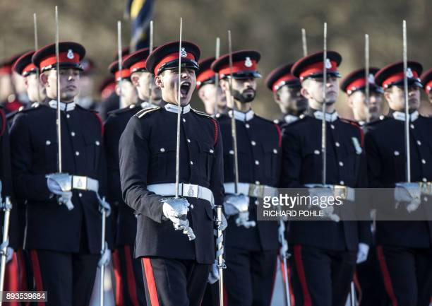 Officer cadets stand to attention as Britain's Prince Harry representing Britain's Queen Elizabeth II inspects the graduating officer cadets during...