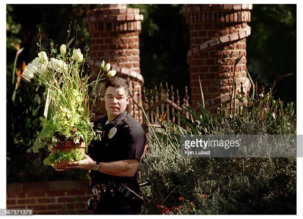 BORDER––––LAPD officer carries flowers delivered to the Bill Cosby family home in Pacific Palisades Friday following slaying of Cosby's son Ennis...
