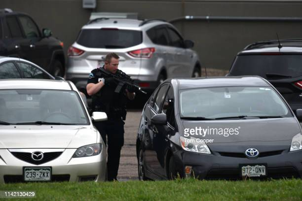 A officer checks vehicles at the scene of a shooting in which at least seven students were injured at the STEM School Highlands Ranch on May 7 2019...