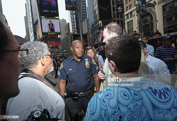 A NYPD officer confronts Andy Golub for body painting a model in the nude in Times Square on August 19 2011 in New York City