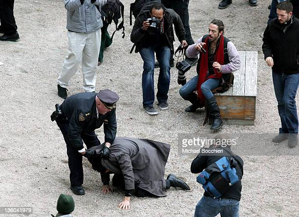 Officer detains a man after activists gained entrance to a private park owned by Trinity Church next to Duarte Square at Sixth Avenue and Canal...
