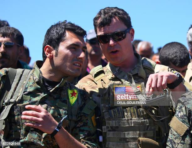 A US officer from the USled coalition speaks with a fighter from the Kurdish People's Protection Units at the site of Turkish airstrikes near...
