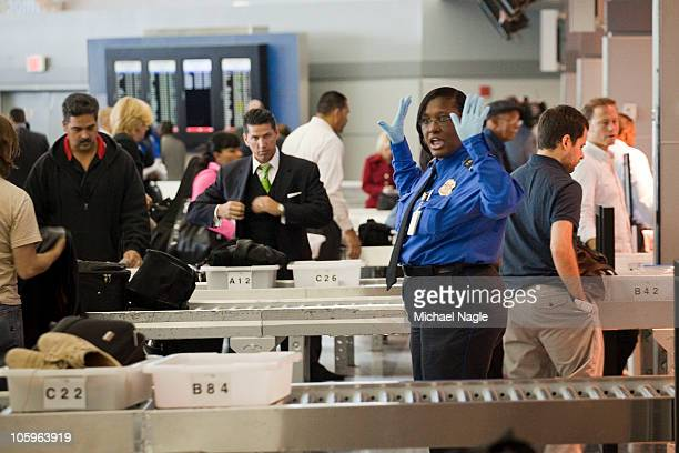TSA officer gives directions to passengers at John F Kennedy International Airport's Terminal 8 passenger security checkpoint on October 22 2010 in...
