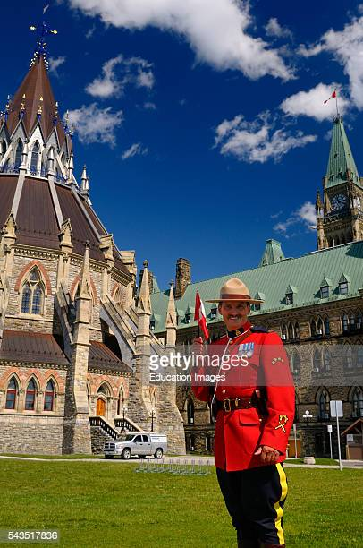 RCMP officer holding flag at Parliament buildings Center Block and Library with Peace Tower in Ottawa