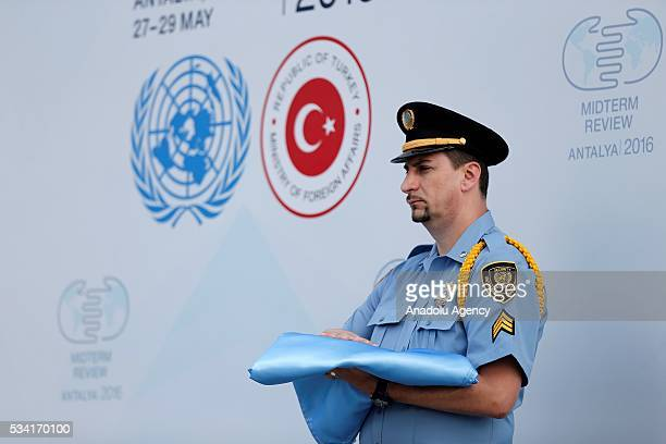 UN officer holds the United Nations flag during the ceremony for the raising United Nations flag at the Titanic Hotel where Midterm Review of the...