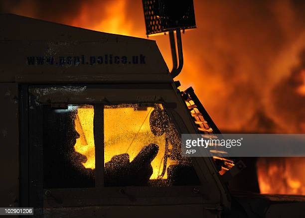 Officer in his Land Rover is sillhouetted by a car burning in a street during a fourth night of Nationalist rioting in Belfast on July 15, 2010. The...